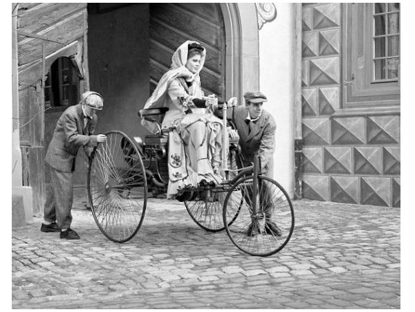 Three-wheel first car with Bertha Benz driving it.